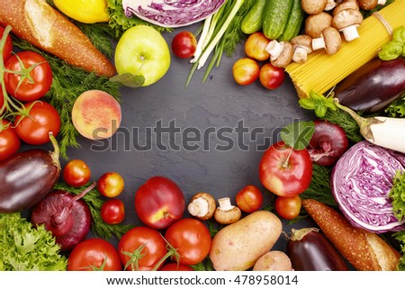 Frame of different food products on a dark surface, top view