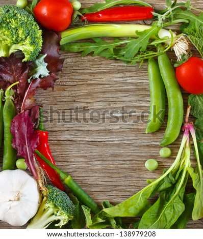 Frame of fresh vegetables and herbs on a wooden background. - stock photo