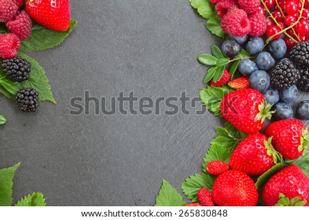 frame  of fresh  wild berries with green  leaves with copy space  on black  background - stock photo