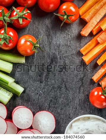 Frame of healthy vegetarian fresh vegetable crudites with sliced carrot and cucumber batons, radish, cherry tomatoes and a vinaigrette savoury sauce on slate with central copypsace - stock photo