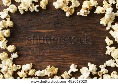 Frame of popcorn on wood background with copyspace