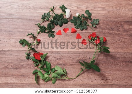 Frame of red roses with green leaves and red hearts on a wooden background. Greeting card. Conceptual photography. Wedding invitation card. Valentine day. Flat lay, top view, copyspace