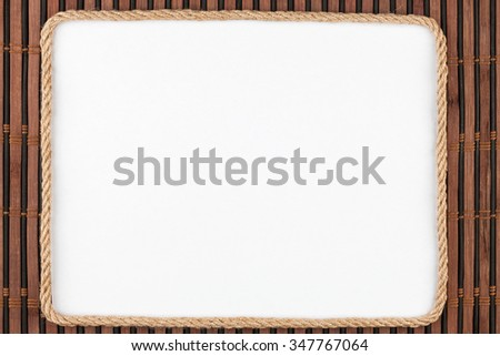Frame of rope, lies on a background of a  bamboo mat, with place for your text - stock photo