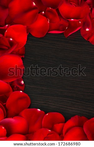 Frame of rose petals on wooden table close-up - stock photo