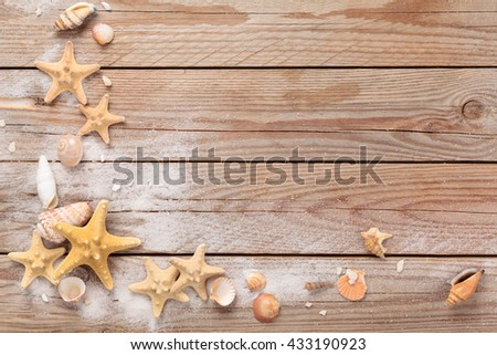 Frame Of Seashells And White Sand On Rustic Wooden Background