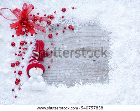 Frame of snow with snowmen on wooden background with space for your text