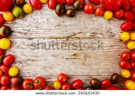 Frame of tomatoes family varieties over a rustic wooden background with copyspace - stock photo