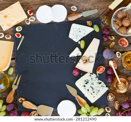 Frame of various types of cheese and appetizer on black cutting board with copy space - stock photo