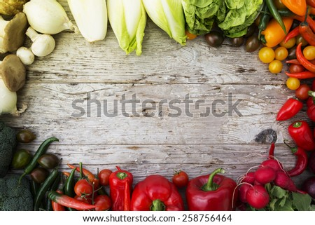 Frame of various vegetables over a rustic wooden background with copyspace - stock photo