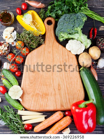 Frame of vegetables, herbs. Harvest, culinary, autumn background. Ingredients for cooking and empty cutting board Copy space