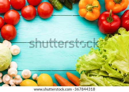 Frame of vegetables with copy space on blue wooden background. Top view - stock photo