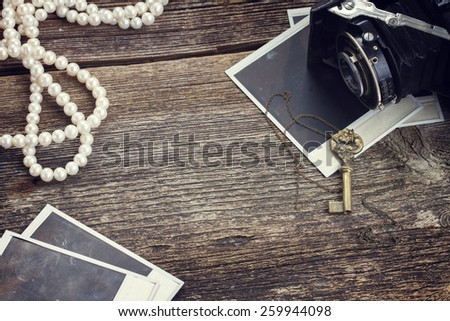 frame of vintage  photo camera on pile of old instant photos on wooden background - stock photo