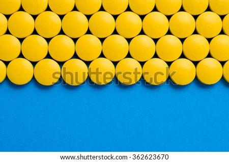 Frame of yellow pills - stock photo