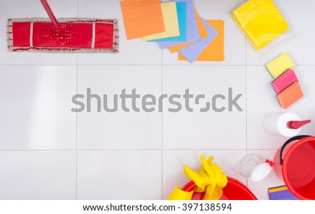 Frame or border of colorful household cleaning products arranged around the sides on a clean white tiled floor with central copy space viewed from above - stock photo