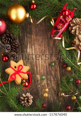 Frame with Christmas tree branches, cookies and ornaments on wooden background - stock photo
