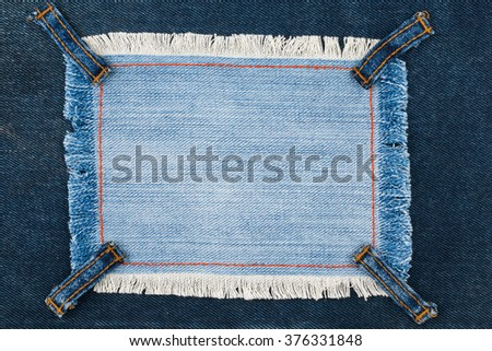 Frame with four straps jeans, lies on the dark denim, with space for your text - stock photo