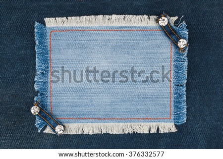 Frame with two straps jeans and rhinestones, lies on the dark denim, with space for your text