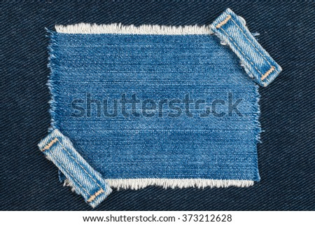 Frame with two straps jeans, lies on the dark denim, with space for your text - stock photo