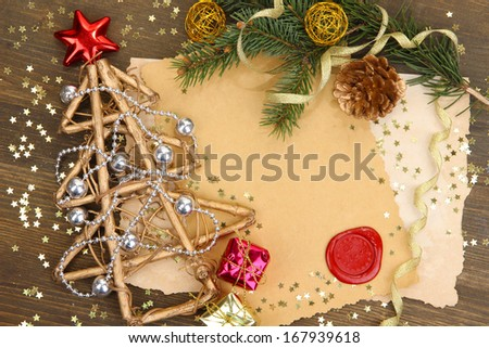 Frame with vintage paper and Christmas decorations on wooden background - stock photo