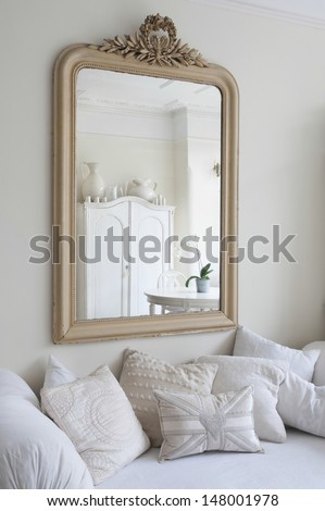 Framed mirror above daybed with cushions - stock photo