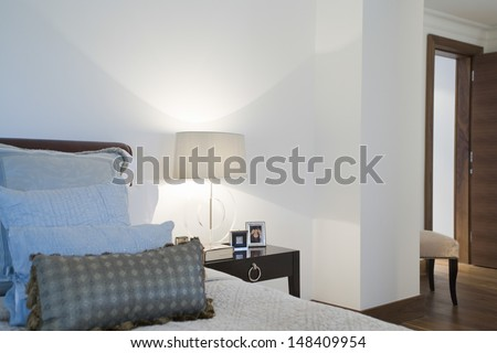 Framed photographs and lamp on side table in bedroom - stock photo