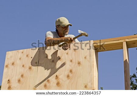 Framing construction contractor installing sub siding on a wood frame wall of a new luxury custom home