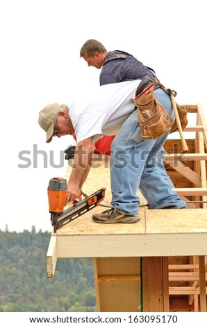 Framing contractor installing roof sheeting over rafters on a new commercial residential construction project - stock photo