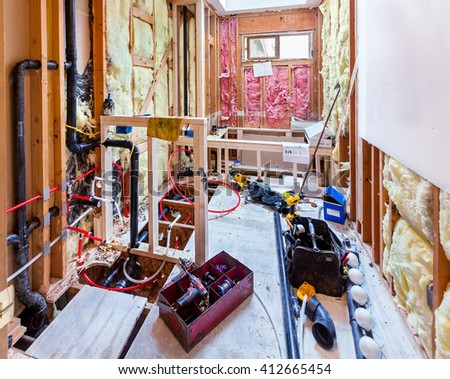 Framing for pony wall and new tub and new plastic plumbing pipes connecting to old copper pipes - stock photo