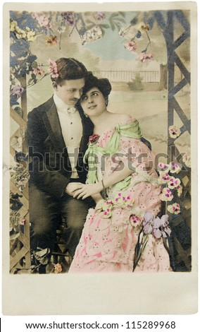 FRANCE - CIRCA 1912. Vintage postcard printed in FRANCE shows hand-tinted photograph of man and woman in romantic pose. Circa 1912. - stock photo