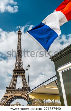 France flag over blue cloudy sky and Eiffel tower in Paris - stock photo
