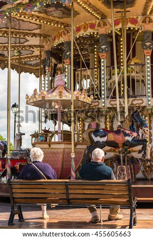 FRANCE, HONFLEUR - MAY 30: an elderly couple sitting on a wooden bench near the carousel on May 30, 2015