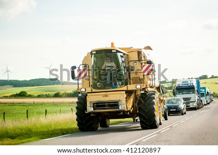 FRANCE, JUL 11, 2011: Agricultural Machine - Special Transport driving on French road with traffic jam behind