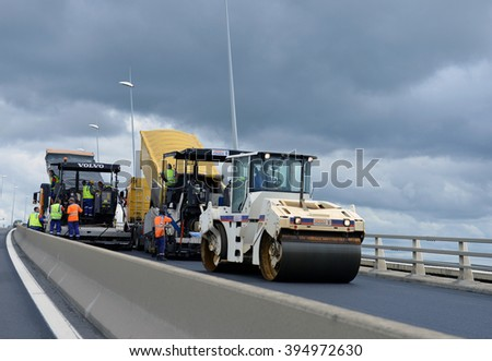France - July 13 2012: On the job site - laying asphalt on the bridge of workers and road construction machinery on July 13 2012, France - stock photo