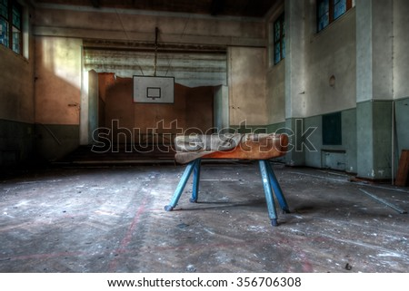 France - May 09.2013: Abandoned sports hall with a pommel horse apparatus in an abandoned school somewhere in France - stock photo