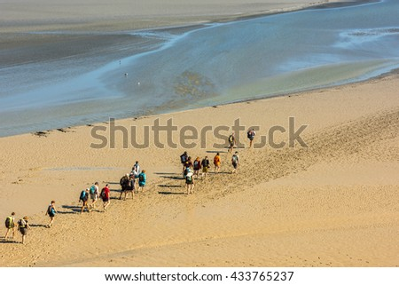 FRANCE, MONT SAINT MICHEL - SEPTEMBER 26: View from walls of Mont Saint Michel on the bay during the low tide with groups of tourists walking. France on September 26, 2015
