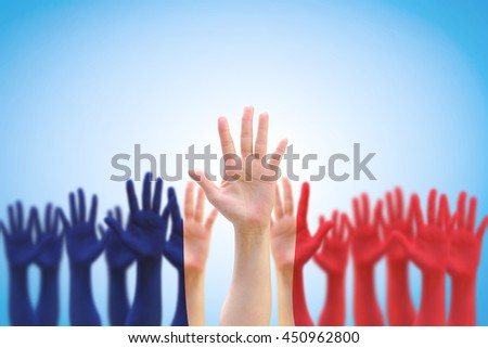 France national flag pattern on leader's fist among blur many people open palm hands crowd group raising up on blue sky background: French Bastille Day, labour day, human rights leadership concept