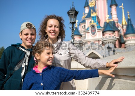 FRANCE, PARIS - 10 SEP, 2014: Young woman with her children (with model releases) are standing near Disneyland castle. - stock photo