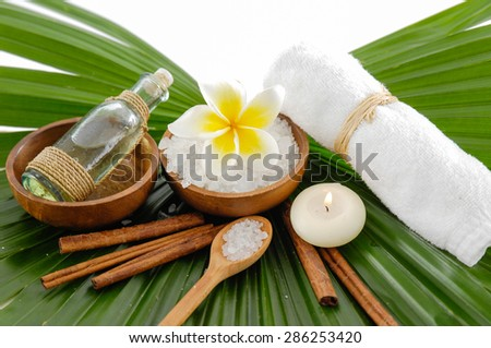 frangipani and candle ,oil ,saltin bowl,towel , on palm leaf - stock photo