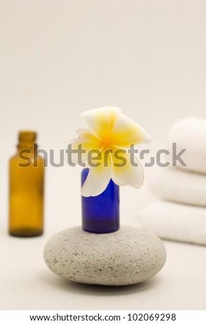 Frangipani flower bottles and towels - stock photo