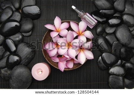 frangipani flower in bowl with candle and oil and pile stones on mat - stock photo