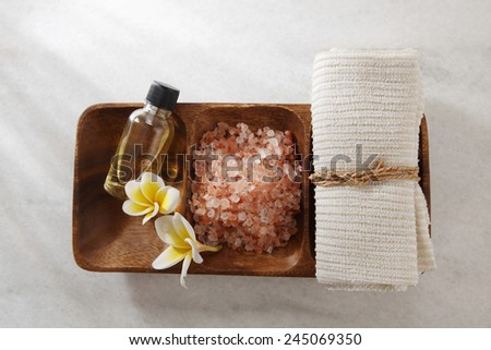 frangipani flower,salt,massage oil and towel in a wooden bowl - stock photo