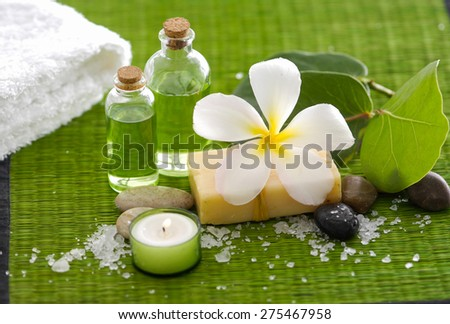 frangipani flower with pile of salt ,candle, oil ,leaf on green mat