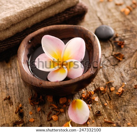 frangipani in wooden bowl ,dry flower petals, towel on old wood  - stock photo