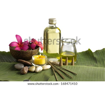 frangipani in wooden bowl of with stones, oil ,candle and green leaves
