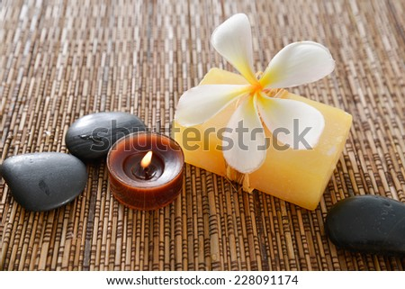 frangipani on soap with candle ,stones on mat  - stock photo