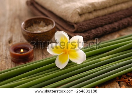 frangipani with grove, candle, towel ,dry flower petals on old wood  - stock photo