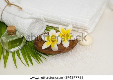 frangipani with oil and towel and palm ,candle on towel   - stock photo