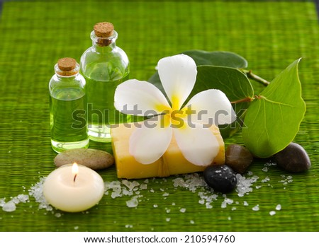 frangipani with stone ,plant with pile of salt ,oil, soap on mat