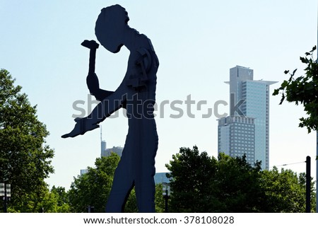 "FRANKFURT AM MAIN, GERMANY - AUGUST 7, 2015: Kinetic sculpture ""Hammering Man"" by Jonathan Borofsky near Frankfurt Messe exhibition area is 21 m high with periodically moving arm holding hammer. - stock photo"
