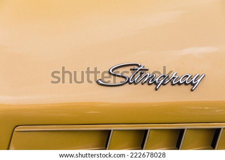 FRANKFURT - AUGUST 15, 2014: Close up of a Corvette Stingray logo of a vintage Cadillac with yellow, beige paint taken on August 15, 2014 in Frankfurt, Germany - stock photo